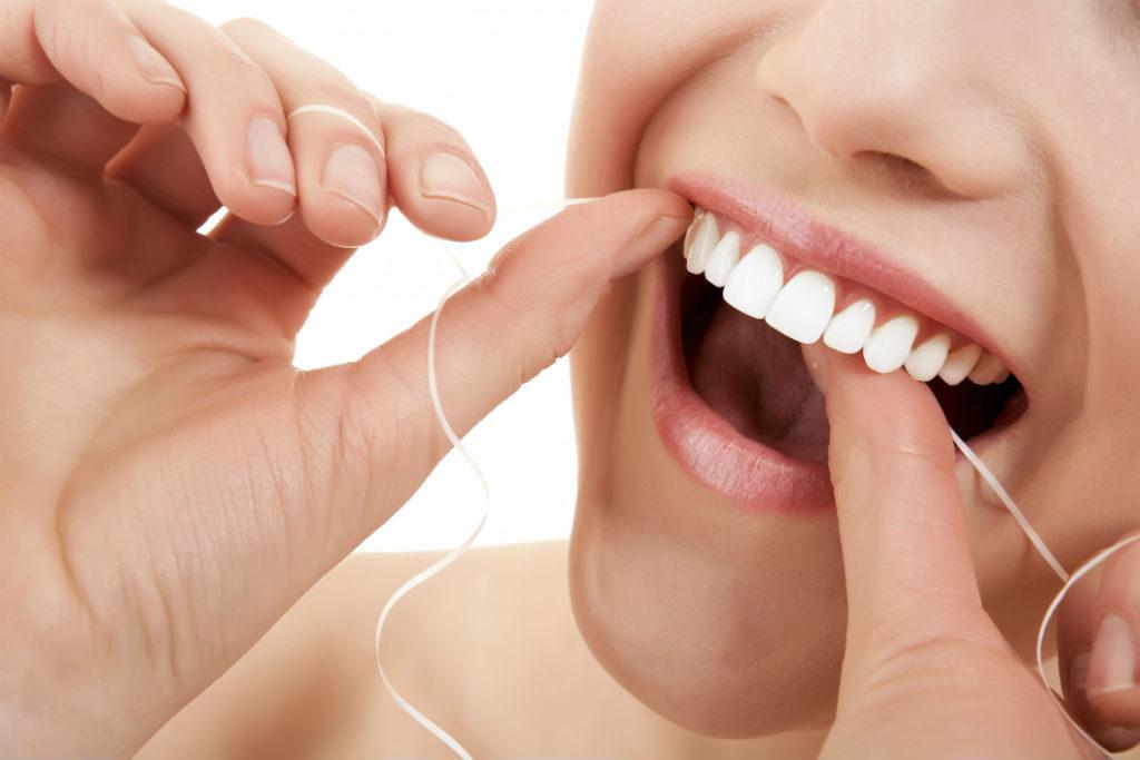 Bild offener Mund von junger Frau Zahnseide reinigend